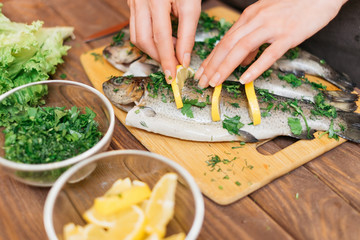 Woman preparing fish with lemons and greenery.