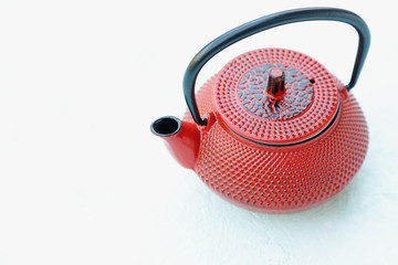 Red cast iron tea pot on gray concrete background, top view, copy space
