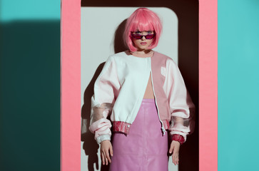 beautiful young woman in pink wig standing in box and looking at camera