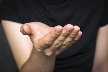 Man`s empty hand with palm up on the dark background.