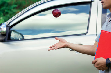 A man is holding textbook and playing apple near his car
