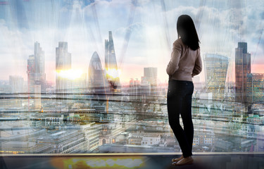 Young woman in suit looking over the City of London at sunrise