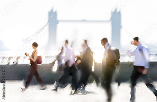 Group of business people walking over London bridge to the