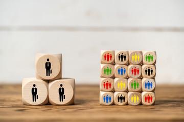 Symbole auf Würfeln verdeutlichen das Konzept von wenigen Großkunden vs. vielen kleinen Kunden