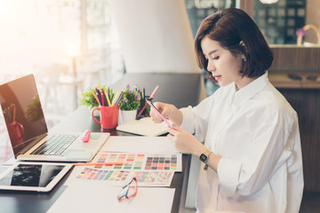 Young woman designer choosing colored pencils and color samples sheets for selection on office desk.