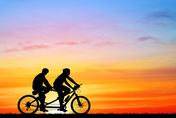 silhouette vintage bike and love couple on sunrise  background