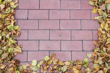 Рамка из осенних листьев выложена на брусчатке из красного кирпича