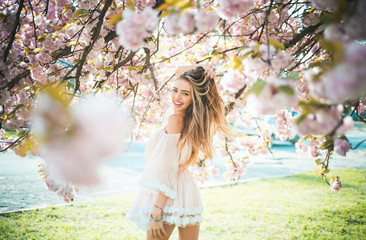 Girl in short pink dress enjoying sunny day in botanical garden. Female playing with long gorgeous blond hair, beauty and hair care products. Sexy woman posing under blooming cherry blossom tree