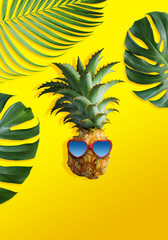 Pineapple with sunglasses and tropical leaves on yellow background summer concept