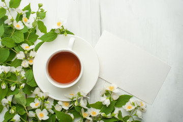 Empty frame with flowers and a cup of tea on a light background. It is possible to use both for inscription, demonstration of fonts, and as a postcard