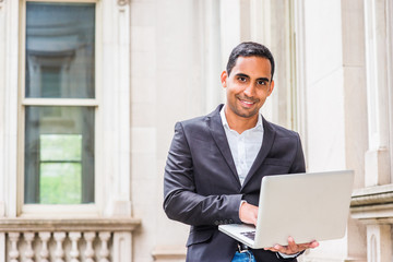 Young Handsome Hispanic American college student studying in New York, wearing black blazer, white shirt, sitting inside old office building on campus, working on laptop computer, looking up, smiling