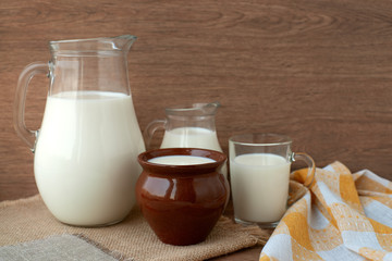 Milk in different dishes. Milk jugs, a glass and a clay pot in a rustic style. A lot of milk on sacking.