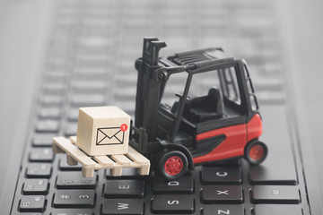Forklift with new email graphic on wooden block over laptop keyboard