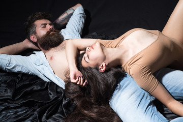 Couple having rest, relaxing after making love. Love and sex concept. Lady with decollete laying on bearded macho. Couple in love on calm faces relaxing in bed, black silk sheets on background.