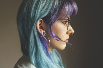 Headshot portrait of serious young woman with blue hair, piercings and glasses