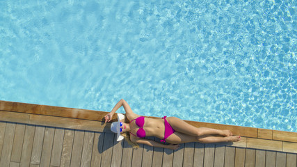 AERIAL: Young woman with amazing physique sun tanning on the edge of big pool.