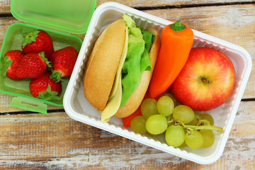Healthy school lunchbox  containing cheese sandwich with lettuce, crunchy yellow pepper and fresh fruit