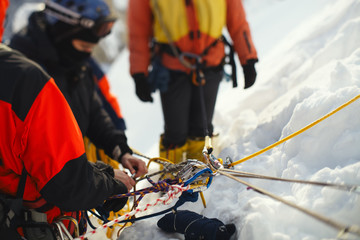 Attaching climbers on a safety rope, close-up.  Tilt-shift effect.