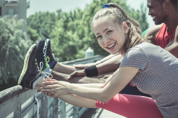 young woman doing fitness and stretching outdoor in park with friends