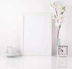 White frame, flower in vase, cup with tea or coffee, clock on wh