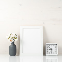 White frame, flower in vase, clock on white table against the wh