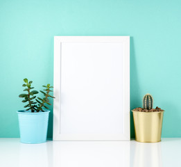Blank white frame, plant cactus on white table against the blue