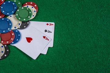 cartas y fichas de poker sobre mesa verde de casino