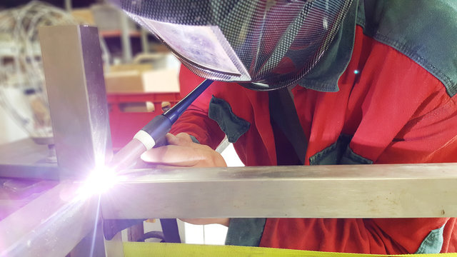Man welds profiles of stainless steel