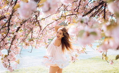 Woman with gorgeous smile having fun in blooming garden. Female with slim sexy body on natural background, wellness and fitness concept. Sensual blond girl in short chiffon dress walking in park