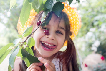 Happy Child Girl Wellcomes Summer Season in the Cherry Tree Garden, Organic Fresh Fruit Concept