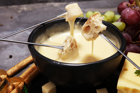 Gourmet Swiss fondue dinner on a winter evening with assorted cheeses on a board alongside a heated pot of cheese fondue