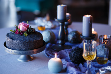 Dark decor with burning candles, old glasses, vintage silverware, textured fabrics in a dark room.
