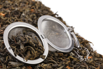 Tea strainer on a chain, with a mixture of dry green large-leaf tea with soursop, isolated on a white background.