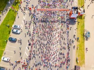 International Marathon Lattelecom 2018. Start on the embankment and people running by the Daugava river and statue of liberty Milda.