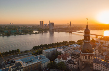 Amazing aerial view of the sunset over Old town of Riga, Vecriga in Latvia. River Daugava, with Domes cathedral and golden cock in the foreground.
