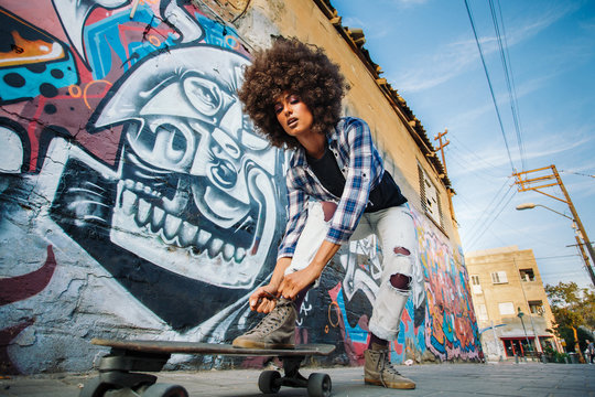 African American girl stands on skateboard with wall on background