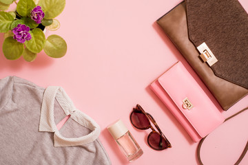 set clothes, a purse and a bag, a comb and sunglasses, a self-stick and eau de toilette. Flowers are next to a pink background. Fashion trends of summer for the women.