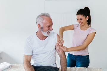 Senior man having massage in rehabilitation center.