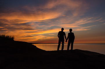 Backlit Couple on large rock overlooking colorful maritime sunset