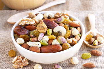 Dried fruits mix and variety of nuts into a bowl made of ceramic on the brown sackcloth background.