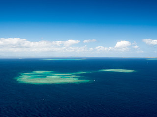 Aerial Landscape View of South Pacific Reef Island Surrounded by Deep Blue Ocean in Summer Weather