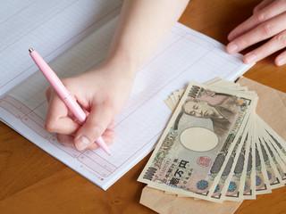 家計簿でお金のやりくりをする女性