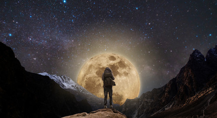 a man standing on mountain peak at night, and full moon on night sky full of stars