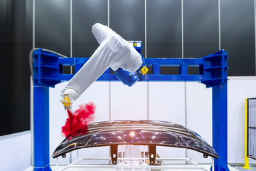 Robotic arm painting spray to the automotive part. High-technology manufacturing concept.