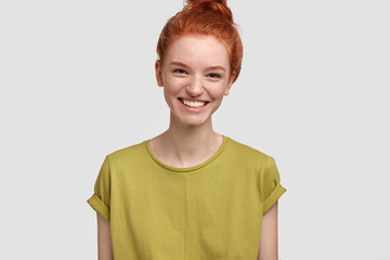 Headshot of pretty female pupil, smiles positively, has appealing appearance, freckled skin, being in good mood after having party with friends, isolated on white background. Emotions and lifestyle