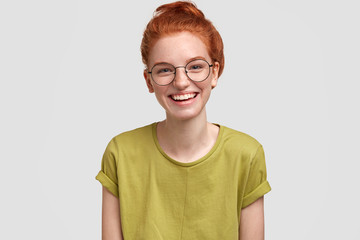 Portrait of happy female with ginger hair, has joyful expression, laughs at good joke, wears spectacles and green t shirt, isolated on white background. People, lifestyle, human emotions concept.