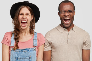 Frustrated mixed raced female and male farmer owners look desperately at camera as have crisis because of bad harvest, stand close to each other, isolated over white background. Two angry coworkers