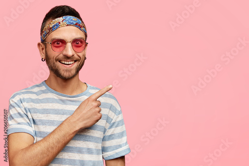 182fa5742c8b Horizontal shot of pleasant looking young hippy male with stubble, wears  stylish pink sunglasses and headband, indicates at upper right corner, ...