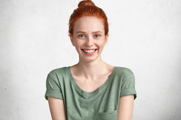 Portrait of red haired freckled female with positive smile, wears casual t shirt, poses against white background. Delighted beautiful ginger student rejoices good news as entered desirable university