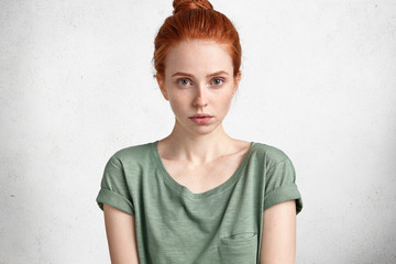 Cropped shot of attractive young foxy female with freckled healthy skin, looks seriously directly into camera, has natural beauty, recieves necessary information, has serious talk with employee